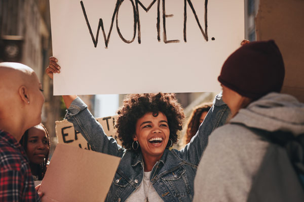"""femal protestor holding up sign that says """"women"""""""