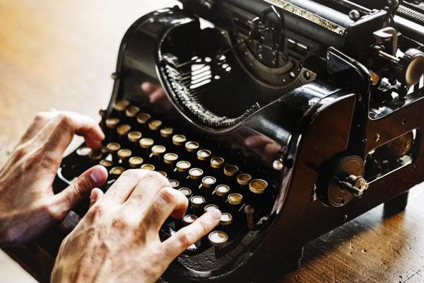 hands typing on a vintage typewriter