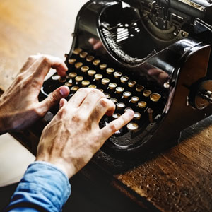 hands typing on a vintage typewriter