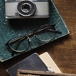notepad, old camea, glasses on a desk