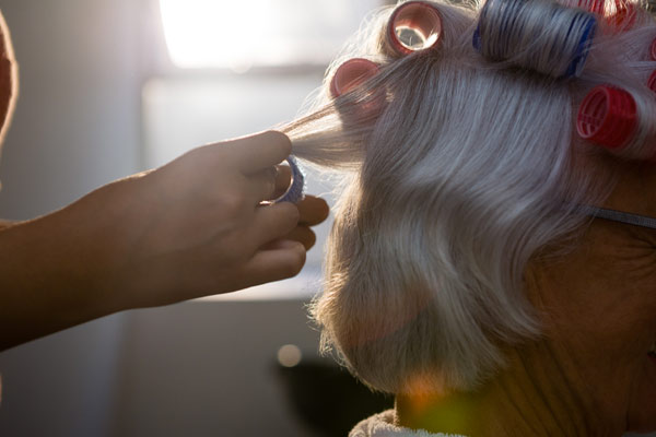 Photo of a woman getting her hair curled at a beauty parlour