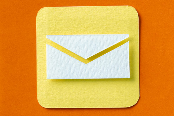Paper cutout of white envelope on a yellow and orange background