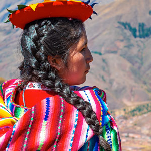 A woman in traditional dress looks out over the Andes mountains