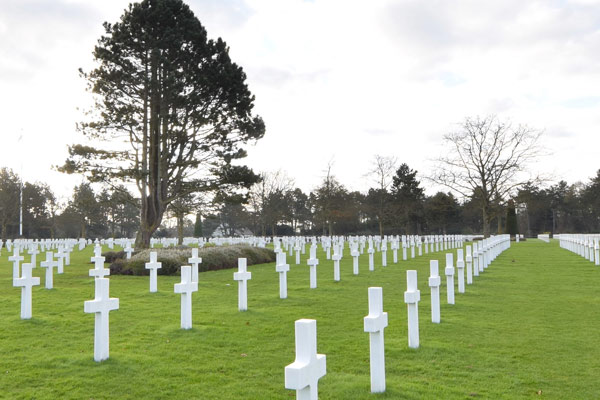 Photograph of a large military cemetary with rows of white crosses