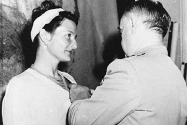 Black and white photo of Virignia Hall getting a medal from General Donovan