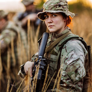 Photo of a woman in combat fatigues carrying an automatic weapon