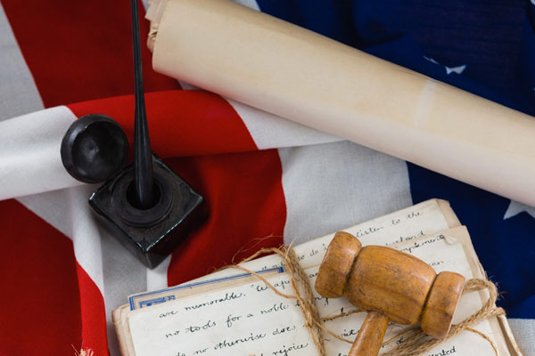 A gavel, court documents, all sitting on an American flag