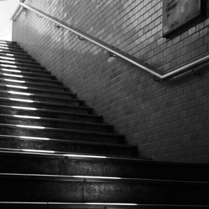 black and white photo of darkened subway stairs leading up to the light