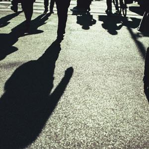 shadows of people walking on a street