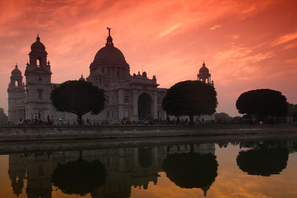 A photo of Victoria Memorial in Calcutta, India reflected in the water at sunset