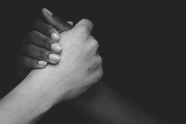 Hands of 2 different people interlocked - one white and one black