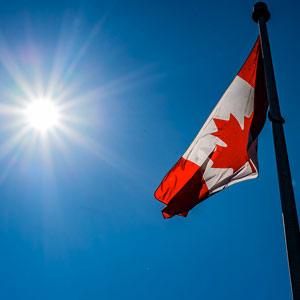 Canadian flag against a deep blue sky and a bright sun