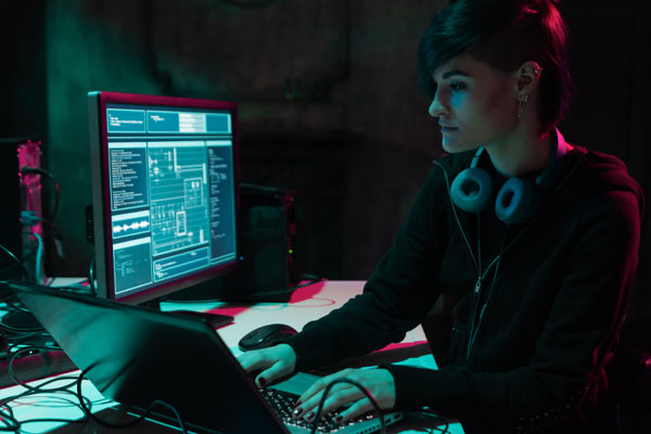 Photo of a woman in the shadows doing programming on a computer