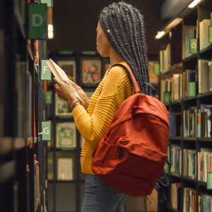 A woman of colour looking through the racks in a library